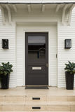 Front door, brown door, white exterior Royalty Free Stock Images