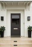 Front door, brown door, white exterior Royalty Free Stock Images