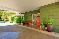 Front door and green house with nice curb appeal. Summer sunny day house exterior of the long green hosue with beautiful curb appeal Stock Photography