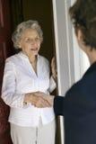 Front door greeting. Senior woman shaking hands at her front door Royalty Free Stock Photography