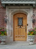 Front door of house with flower pots Royalty Free Stock Images