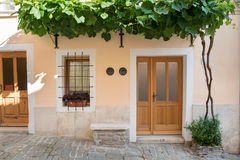 Front door of a mediterranean house with grapes in Sloven Stock Photo
