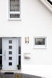 Front door of a modern house. Architectural background of the front door of a modern white painted house Royalty Free Stock Photo