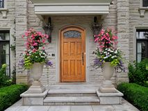 Front door of stone house with large flower pots. Wooden front door of stone house with large flower pots royalty free stock photo