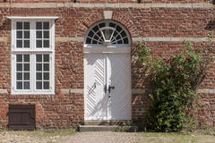 Front door, transom windows and climbing rose at a typical brick Stock Photos