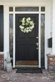 Front door of an upscale home. Vertical shot of a front door of a home with a wreath, brick flooring and reflection in the windows Stock Photo