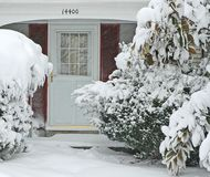 Front Door and Walkway In Big Snowstorm. Front walkway and door to a suburban house during a heavy winter snowstorm Stock Images
