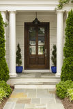 Front door with white pillars. Slate tile entrance way, potted plants with shrubs, trees and mulch with a traditional porch light Royalty Free Stock Photo