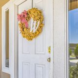 Front door with wreath and reflective glass window. White front door of a house with reflective glass panels on both sides. Yellow ruffled wreath with a letter stock image