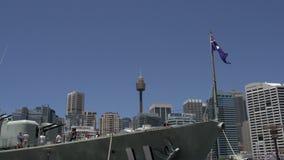 Front eines großen Marineschiffs mit der australischen Flagge mit dem Sydney-Turm und der Skyline am Hintergrund stock video