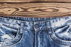 Front empty pockets on blue jeans on old rustic wooden brown planks stock images