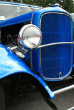 Front end of classic car. Front end of a classice car blue, with headlight stock images