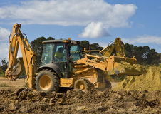 Front end loader with backhoe. In action onmajor housing construction project royalty free stock photos
