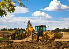 Front end loader with backhoe in action. Onmajor housing construction project royalty free stock photos