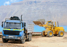 Front end loader and dumper; Graciosa, Spain. Front end loader loading a truck on a shore of Graciosa; Canary islands, Spain Stock Images