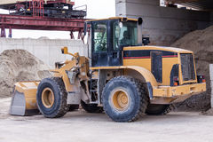 Front end loader. With its bucket or scoop down parked in front of a warehouse on paving royalty free stock image