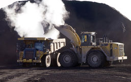 Front End Loader Loading Dump Truck. Front end loader loading a dump truck with coal from a coal pile, steam rising from the dump truck Royalty Free Stock Image