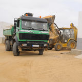 Front end loader loading dumper. Front end loader loading a truck on a shore of Graciosa; Canary islands, Spain royalty free stock images