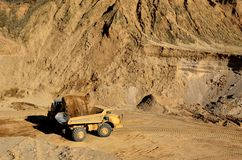 Front-end loader loading with sand a heavy dump truck in quarry. Front-end loader loading with sand a heavy dump truck in a mining quarry royalty free stock photos