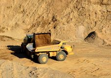Front-end loader loading with sand a heavy dump truck. In a mining quarry stock photography