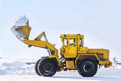 Front-end loader. Novyy Urengoy, Russia - April 6, 2013: Yellow front-end loader loads a snow in a truck in the city street royalty free stock photo