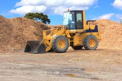Front end loader. With piles of chip bark ready to be loaded and moved royalty free stock image