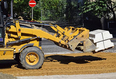 Front end loader at the road construction. Front end loader works at the road construction Royalty Free Stock Images