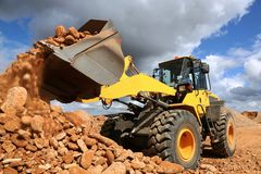 Front End Loader Tipping Stone. Front end loader dumping stone and sand in a mining quarry stock photo