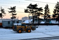 Front-end loader with wheels on a construction site in winter against the backdrop of sunset and spruce trees. stock photos
