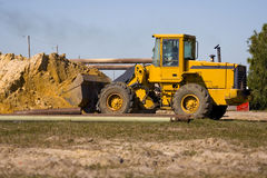 Front end loader at work. A Front end loader at work with a shovel full of dirt Royalty Free Stock Photography