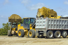Front end loaders at work. A pair of front end loaders team up to fill a dump truck Stock Images