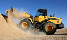 Front End Loading Digging in Sand. Front end loader dumping stone and sand in a mining quarry royalty free stock images