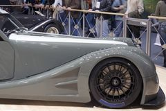 Front end of a sports car. Visitors at the Geneva Motorshow look at a sports car modelled on a classic style Royalty Free Stock Image