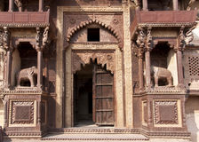 Front entrance of Jehanghir Mahal Palace. Elephants, balconies, and elaborated arches with delapidated wooden door Royalty Free Stock Photos
