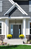 Front Entrance of a Residential Home. Front Entrance of a Residential House with Yellow Chrysanthemum Flowers on Porch Royalty Free Stock Photo