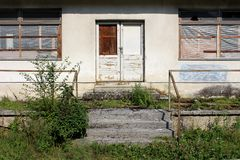 Front entrance to an abandoned house with destroyed windows and locked doors surrounded with plants covering concrete steps and. Front entrance to an abandoned stock photos