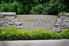 Front entrance to Lincoln Park Zoo in Chicago, Illinois. Front stone entrance to Lincoln Park Zoo with yellow daffodils and green trees in Chicago, Illinois Royalty Free Stock Photos