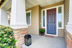 Front entry door with concrete floor porch and flowers pot Stock Image