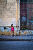 Cuban girl swinging bag in the streets of camagues royalty free stock image
