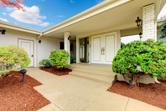 Front exterior entrance to white and beige home with double door Stock Images