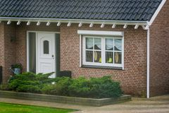 Front exterior of a luxurious dutch bungalow with a garden, front door with decorated window, home in a small village of the. A front exterior of a luxurious royalty free stock photo