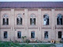 Front facade of an abandoned building with broken windows. Stock Images