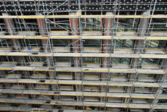 Front facade of a building under construction. High angle close up view of the front facade of a highrise multi-story building under construction or renovation stock photos