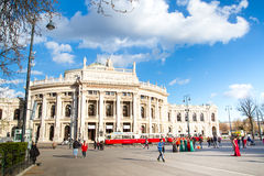 Front facade of Burgtheater, red tram and people on the square, Vienna Stock Image