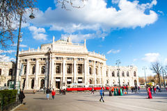 Front facade of Burgtheater, red tram and people on the square, Vienna Stock Photos