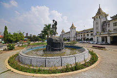 Front Facade della stazione ferroviaria centrale di Rangoon con la fontana rotonda dello stagno decorata con le statue immagini stock libere da diritti