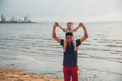 Front father dad and baby boy son lifestyle sitting on shoulders. At sea beach royalty free stock images