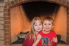 In front of the fireplace. Young children sitting by a fireplace Royalty Free Stock Images