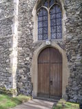 Front of Flint Church. The front of an old church made from flint. You can see the glass windows, with leading, and the heavy wooden door of the church Royalty Free Stock Image