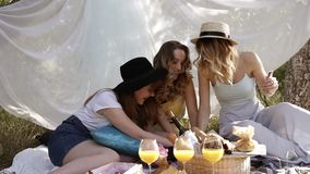 Front footage of three young attractive girls playing card game. Picnic, bachelorette concept. Outdoors, white cloth on. The background stock footage